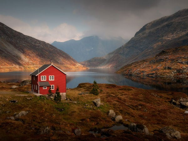 This house with red exterior may have a unique purpose. It can be easily identified in this wilderness. It sticks out and helps the owner to get home easily or stranded hikers to easily ask for help if needed.
