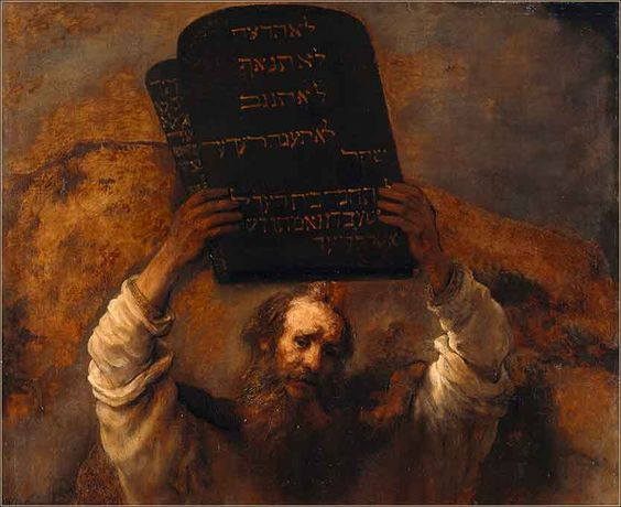 The ten commandments in stone tablets on the hands of Moses.