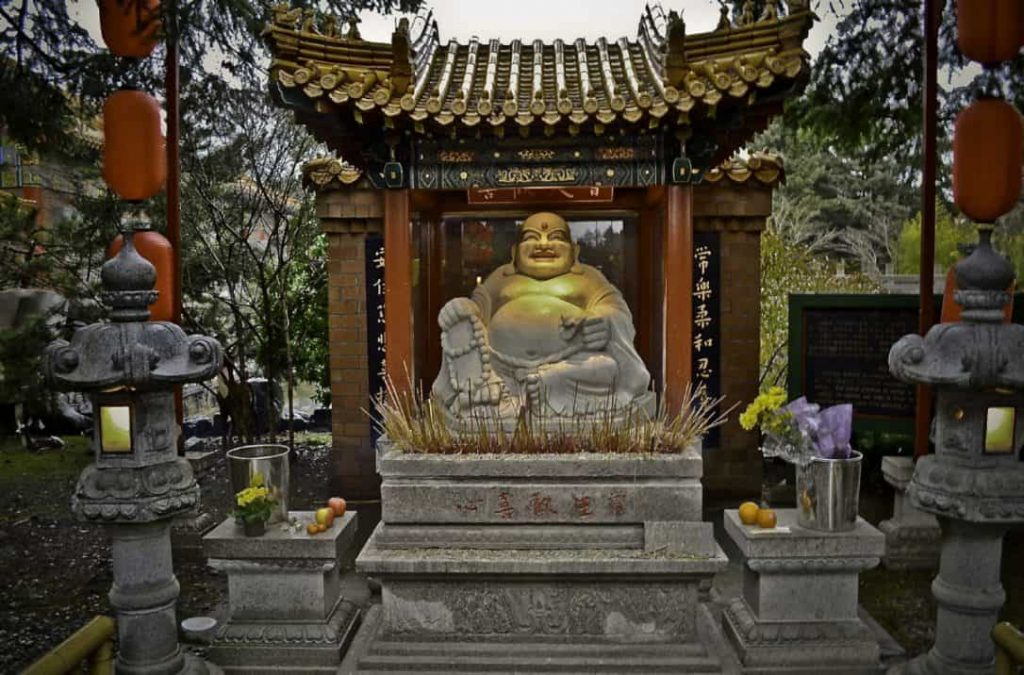Incense, flowers, and fruits are offered to this statue of Laughing Buddha.